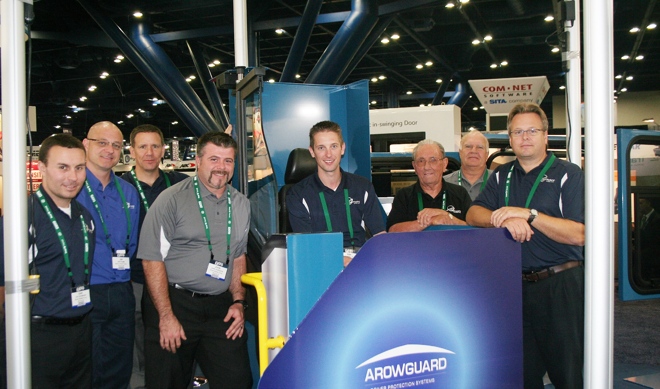 A group shot of 8 men attending a trade show