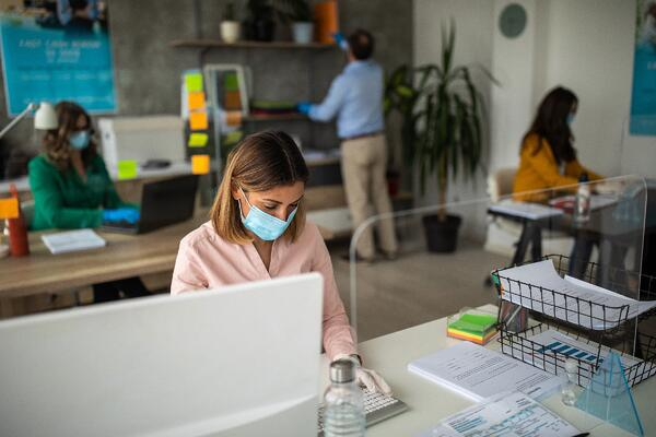 Woman in face mask works at her desk in an open office, socially distancing from other staff also in masks.